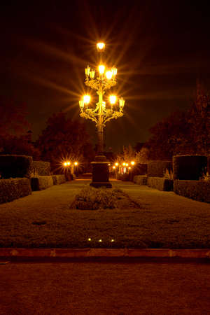 Ornamental lamppost in beautiful romantic night garden, candles, solitary, warm