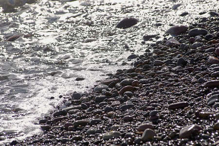 Small rocks beach shore, unfocused background, nobody, foreground, sunny, big and small stones