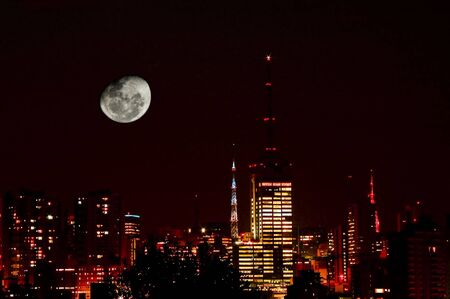 archtecture: Night shot of Moon in city skyline with red filter. Stock Photo