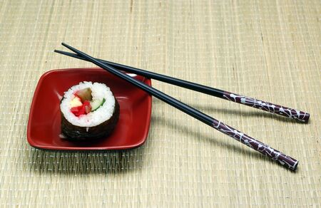 hashi: Individual Sushi in a square plate and hashi.