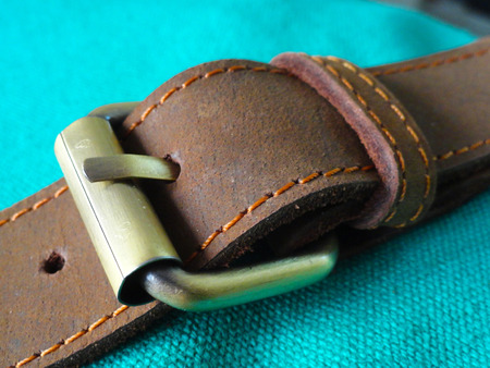 buckle: Brown leather belt with brass buckle on  Green Cotton Cloth Stock Photo