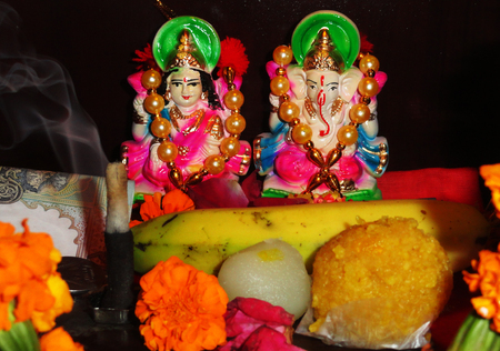 devotional: Devotional Goddess Maa Lakshmi and Lord Ganesha Statue with Some Sweets and Fruits Stock Photo