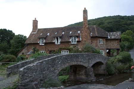 Small Bridge leading to an old English cottage photo