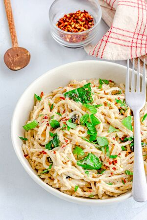 Spaghetti pasta in White Sauce Garnished with Basil Leaves Vertical Top Down Photo Фото со стока
