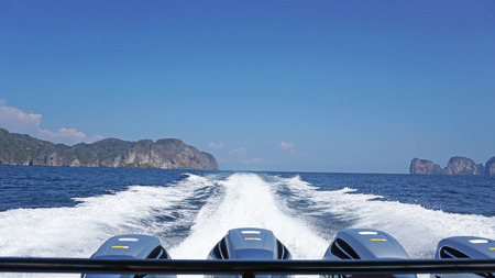 View of the back of the boat. Waves from the engines of a high-speed boat. It offers a landscape of sea, green hills and blue sky. White clouds hung over the Islands. Travel by sea. Banque d'images - 124628789