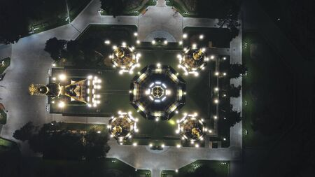 Bright Church with golden domes and crosses. Glows in the night Park. Drone footage. Top and side view. Evening Cathedral in the Park. Bright temple. Modern design of the old building. Lots of lights.