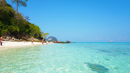 Beautiful beach, clear water and white sand. People relax on the beach. Paradise island. You can see the bottom through the water. Green trees, palm trees. Tourist vacation. Phi Phi Islands, Thailand. Editorial