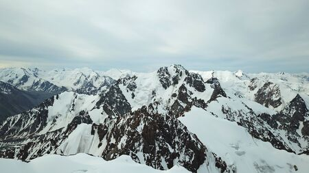 View of the snowy peaks from the drone. Highest peak. You can see huge rocks, cliffs, avalanches, and the shadow falls on them. At an altitude of more than 4300 meters. Mountains Of TRANS-Ili Alatau.