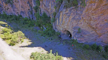 Top view of the cave, forest, rocks and road. A group of tourists walking along the trail. There is a huge cave in the rock. Green coniferous forest, trees and grass grow on the rocks. The river runs. 版權商用圖片