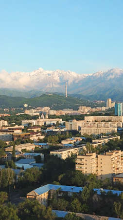Bright color sunset over the city of Almaty. Huge clouds over the mountains and the city shimmer from bright blue to yellow and dark blue. Tall houses and green trees, cars driving on the roads.