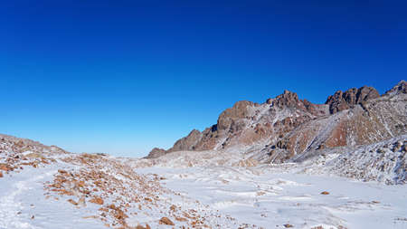 High rocks covered with snow. The Tuyuk Su Glacier. The view from the drone to the tops of the peaks. Completely surrounded by winter mountains. blue clear sky and bright sun. Shadows from mountains
