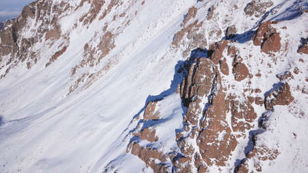 Huge rocks covered with snow. Dangerous terrain. High mountains, cliffs, and large rocks. Shadow from the suns rays. Top and side view from the drone. An epic place. The Mountains Of Almaty. 写真素材
