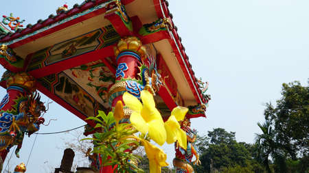 Chinese temple on Koh Chang island of Thailand. Bright colors of the temple, dragon and elephant sculptures. Flowers all around. The smoke from the sticks is coming. Hieroglyphs on the walls of bell.