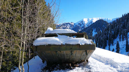 Abandoned military vehicles in the snowy mountains. Retro off-road machine military years. Machine in the mountains and forest. Blue sky and shadows. Abandoned tank on top of a hill.