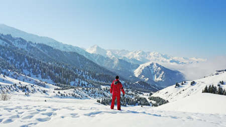 The guy looks at the snow hills and clouds. Mountainous terrain, all covered with fresh snow. Blue sky and huge clouds float along the gorge. On the slopes of a small forest, coniferous trees. Foto de archivo