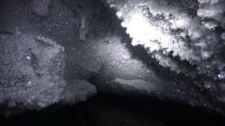 In the mountains inside the Bogdanovich glacier, in an ice cave. Snow and ice growths on the walls of the cave. The beam from the lantern on the stalactites. Light steam in grotto. Hike inside cave