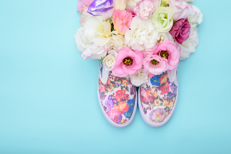 Beautiful gumshoes with flowers inside on bright background Stock Photo