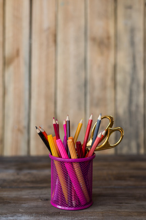Scissors and colorful pencils of violet yellow pink red and orange in stationary cup on wooden table and background. Copyspace school concept Stock Photo