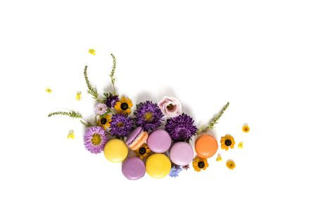 postcard background: Macarons and flowers wreath on a white background. Colorful french dessert with fresh flowers. Top view Stock Photo