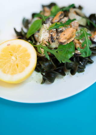 Black pasta with seafood in white cream sauce and lemon. Blue background Stock Photo