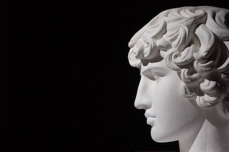 classical greek: Plaster head of sculpture, black background Stock Photo
