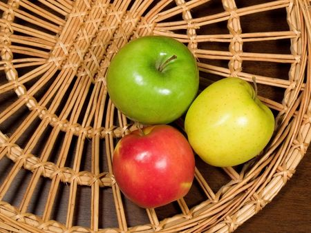 vitamines: Three colored apples on wicker plate at the table