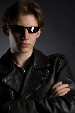 A young man in leather jacket and sunglasses, black background photo