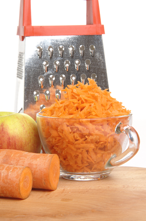 Grated carrots and aple in a cup on a white background photo