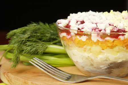 Russian traditional herring salad in glass bowl photo
