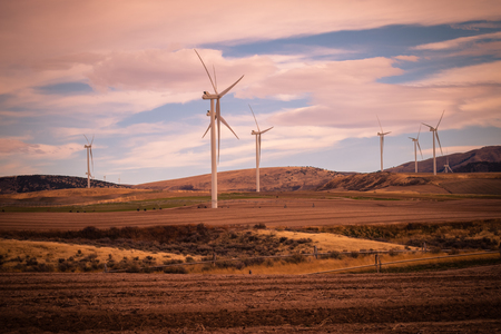 A wind turbine canvases the countryside, as cropland does double-duty producing green energy for Idaho. Stock Photo