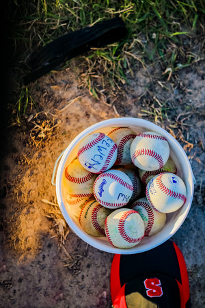 A bucket of baseballs with marker pen writing