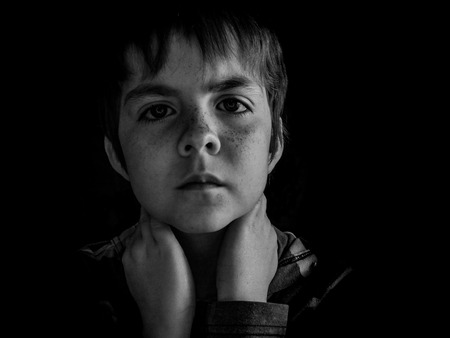 Black and white portrait of a young boy using a ring light, with reflection in his eyes. Stock Photo