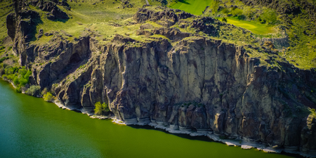 The cliffs along the Snake River in Twin Falls, Idaho look like icy rock formations as they meet the water at the shore. Stock Photo