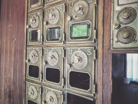 A wall of vintage mailboxes with old dial locks from the US Postal Service.
