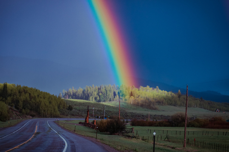A rainbow ends and brightens a group of trees on a country hillside that surrounds the road. Stock Photo