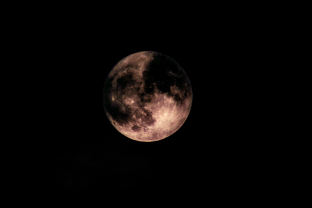 The clouds covering the moon make it appear as if there is a dark hole on the surface. Stock Photo