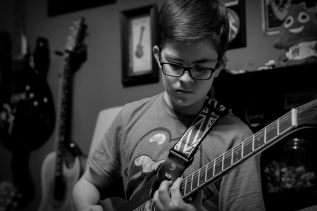 A simple black and white candid of a teen playing his guitar.