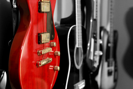 Dual tone wall of guitars, focused on red.