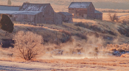 A vintage house and barn from an old farm overlook a creek that is steaming from the chilly Autumn temperatures.