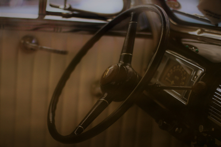 A steering wheel inside a vintage car.