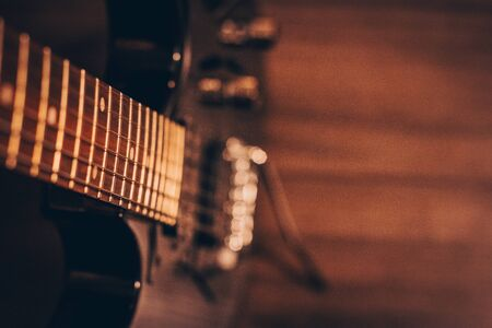 A closeup of a black guitar focused on the metal strings, as it fades to a blurred bokeh background.