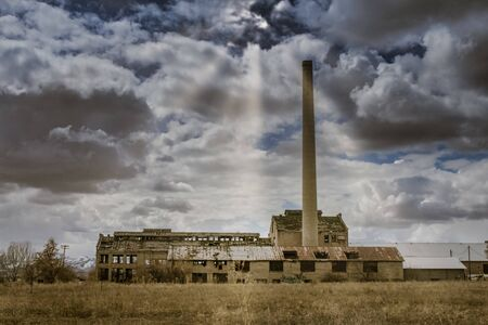 The cloudy sky opens above the Franklin County Sugar Factory near Preston, Idaho and shines soft sun rays on the building.