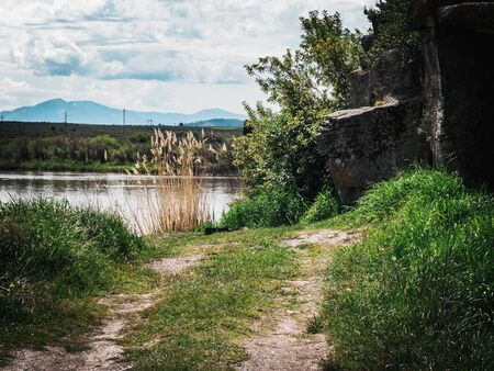A country dirt road ends at the shore of a pond and becomes a nice little spot to relax and fish, surrounded by grass and rocky cliffs.