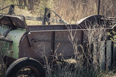 An old vintage hay baler cart sits in a farm field surrounded by grass and bushes. It is now being used as lawn decor and a flower planter.
