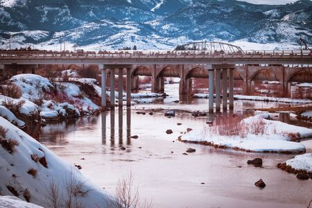 The Bear River Dam in Grace, Idaho in winter. Sun sets on still and shallow water surrounded by snow-covered cliffs and mountains in this rural Idaho scene.