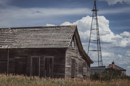 An old farmhouse sits abandoned, with a large metal tower against a cloudy blue sky.