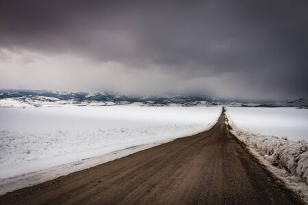 Dark storm clouds roll in over this dirt country road that runs down the middle of a snow-covered field in rural Idaho.