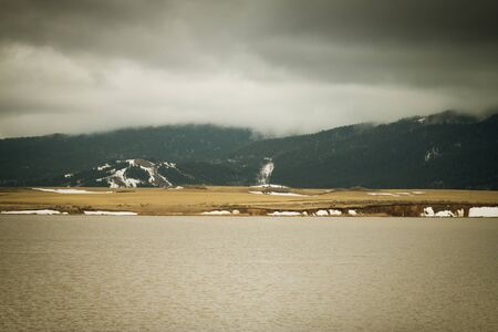 Fog covers the mountainside overlooking Alexander Reservoir, as the last of the snow melts in a field during Spring.