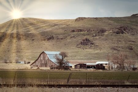 A vintage dairy farm sits below a rocky hillside with the sun setting behind the mountain, while casting beams upon the field below. Stock Photo