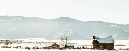 The ruins of an old farm sit in a field against a frozen winter background of snowy mountains. Stock Photo